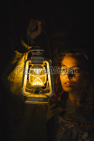 young woman holding storm lantern in