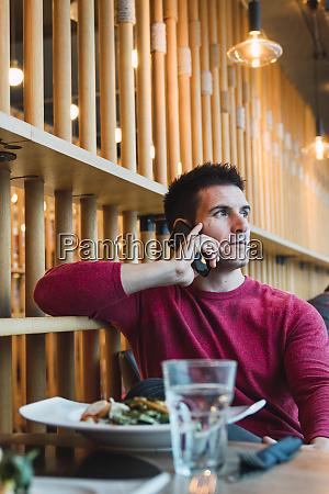 businessman sitting in restaurant using his