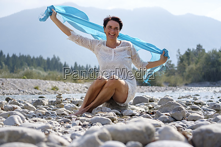 happy woman holding swaying blue scarf