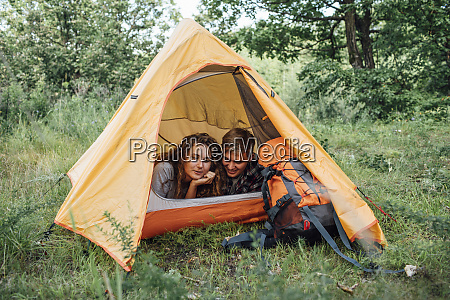 young couple camping in nature lying