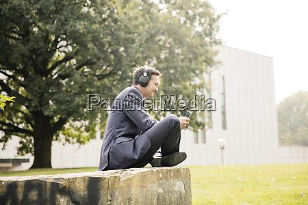 businessman in city park wearing headphones