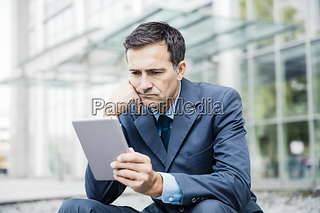 serious businessman using tablet in the