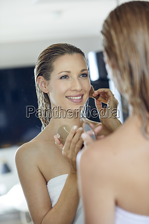 mirror image of smiling blond woman