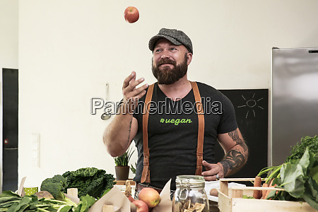 vegan man juggling with apples in