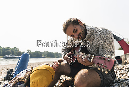 happy young couple playing guitar at