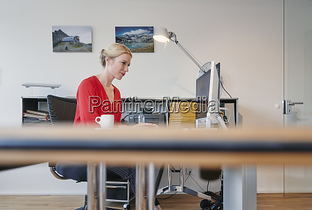 young woman working on computer at
