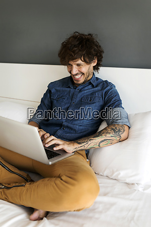 happy tattooed man sitting on bed
