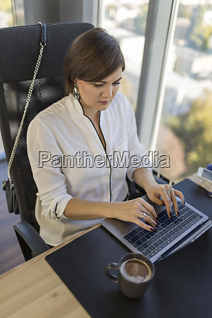 woman using laptop at desk in