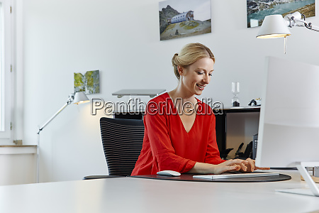 smiling young woman working on computer