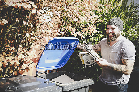 portrait of laughing man recycling waste