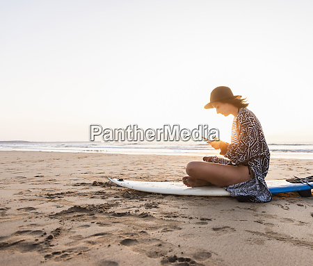 young woman sitting on surfboard at