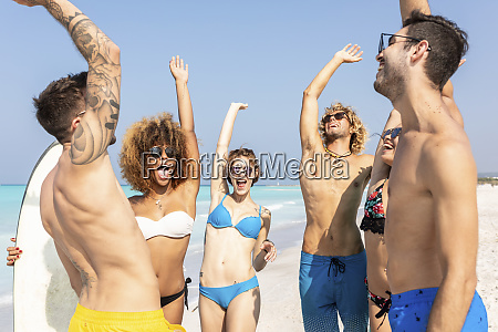 happy friends cheering on the beach