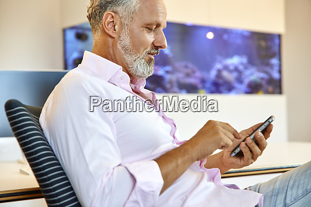 businessman sitting in office using cell