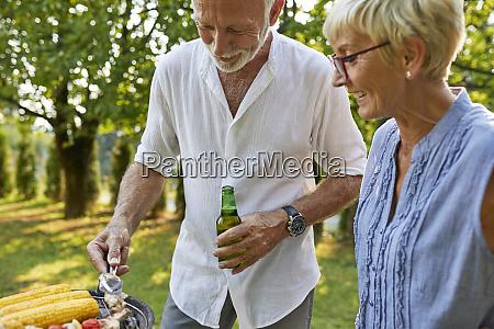 senior couple having a barbecue in