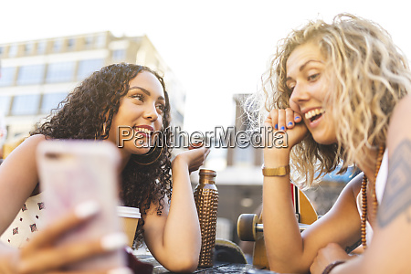 two happy friends sharing cell phone