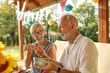 senior couple eating tomatoes on a