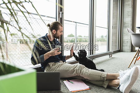 young businessman with laptop sitting on