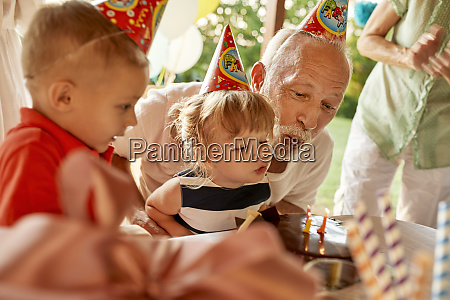 grandfather and grandchildren blowing out candles