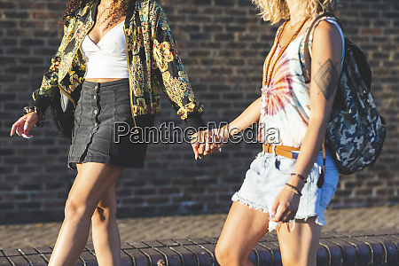 two young women holding hands walking