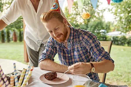 man eating cake on a birthday