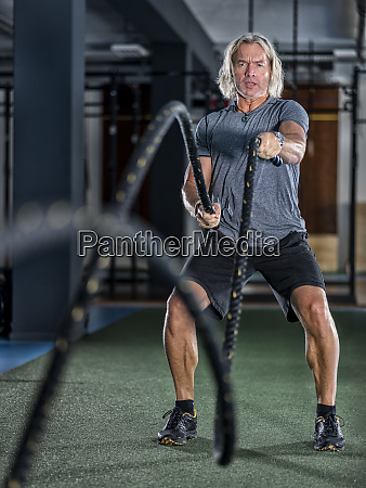 athletic mature man exercising with battle