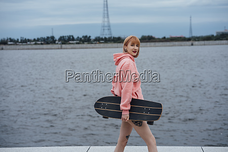 young woman holding carver skateboard walking