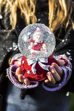 girls hands holding snow globe with