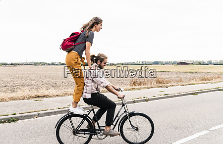 happy young couple riding together on