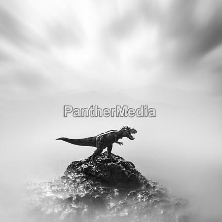 a toy dinosaur on a stone