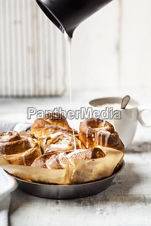 garnishing home baked cinnamon buns with