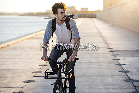 young man with backpack riding bike