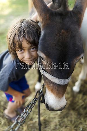 portrait of smiling boy cuddling mule