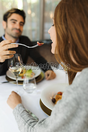 mman letting woman taste the food