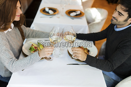 smiling couple clinking wine glasses in