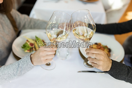 close up of couple clinking wine