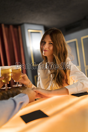 portrait of smiling woman clinking beer