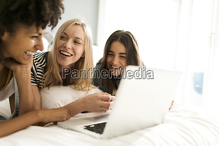 three happy girlfriends lying on bed