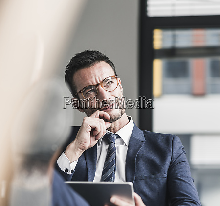businessman using digital tablet sitting in