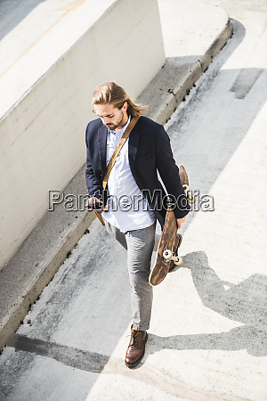 young businessman carrying skateboard using smartphone