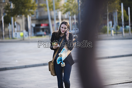 young woman with longboard and snack