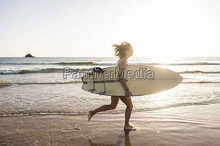 young woman running on beach carrying