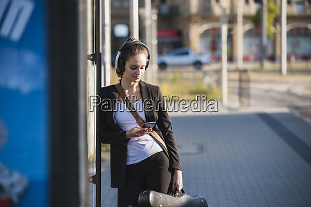 young woman with headphones and cell