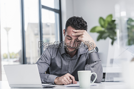 tired businessman sitting in office