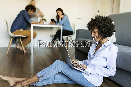 smiling woman sitting on floor using