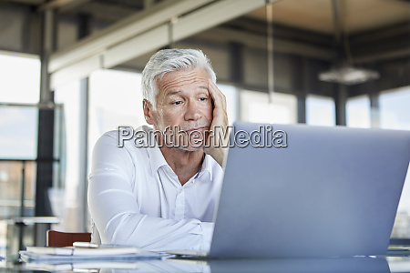 bored businessman sitting at desk using