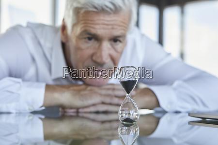 businessman sitting at desk watching hourglass