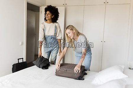 two smiling women with baggage arriving