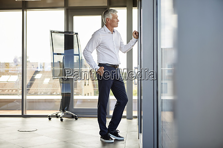 worried businessman standing in office looking