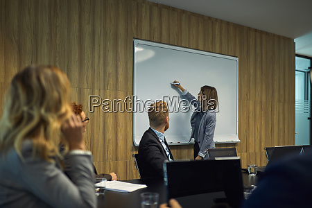 business people looking at businesswoman writing