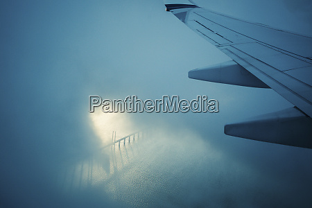 airplane wing flying through clouds over